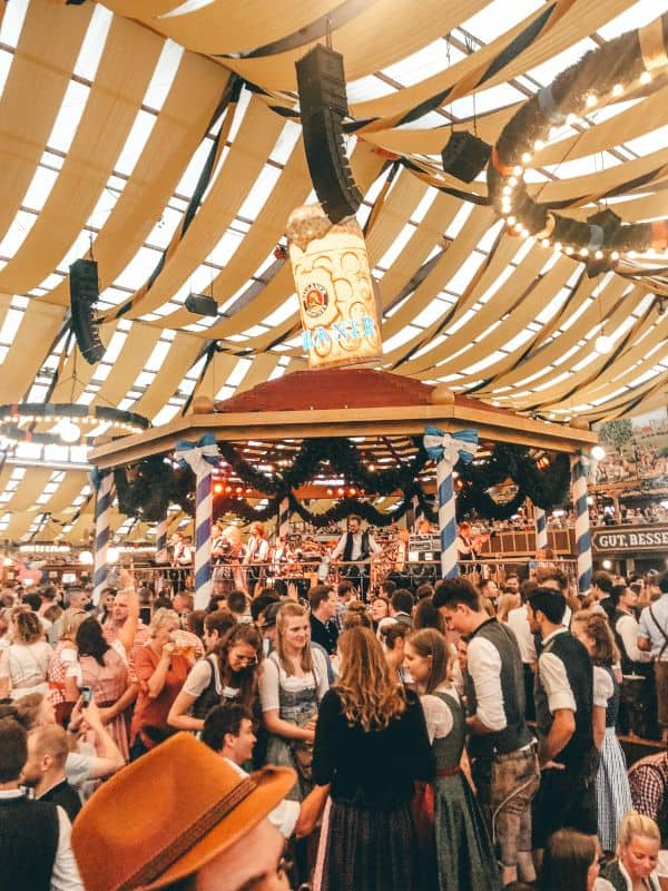 Party goers standing inside a marque in front of stage with a giant beer on top