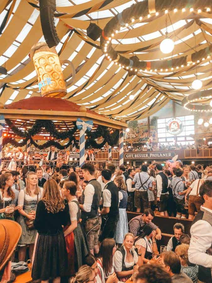 party goers in front of stage with a large beer on top inside a marque