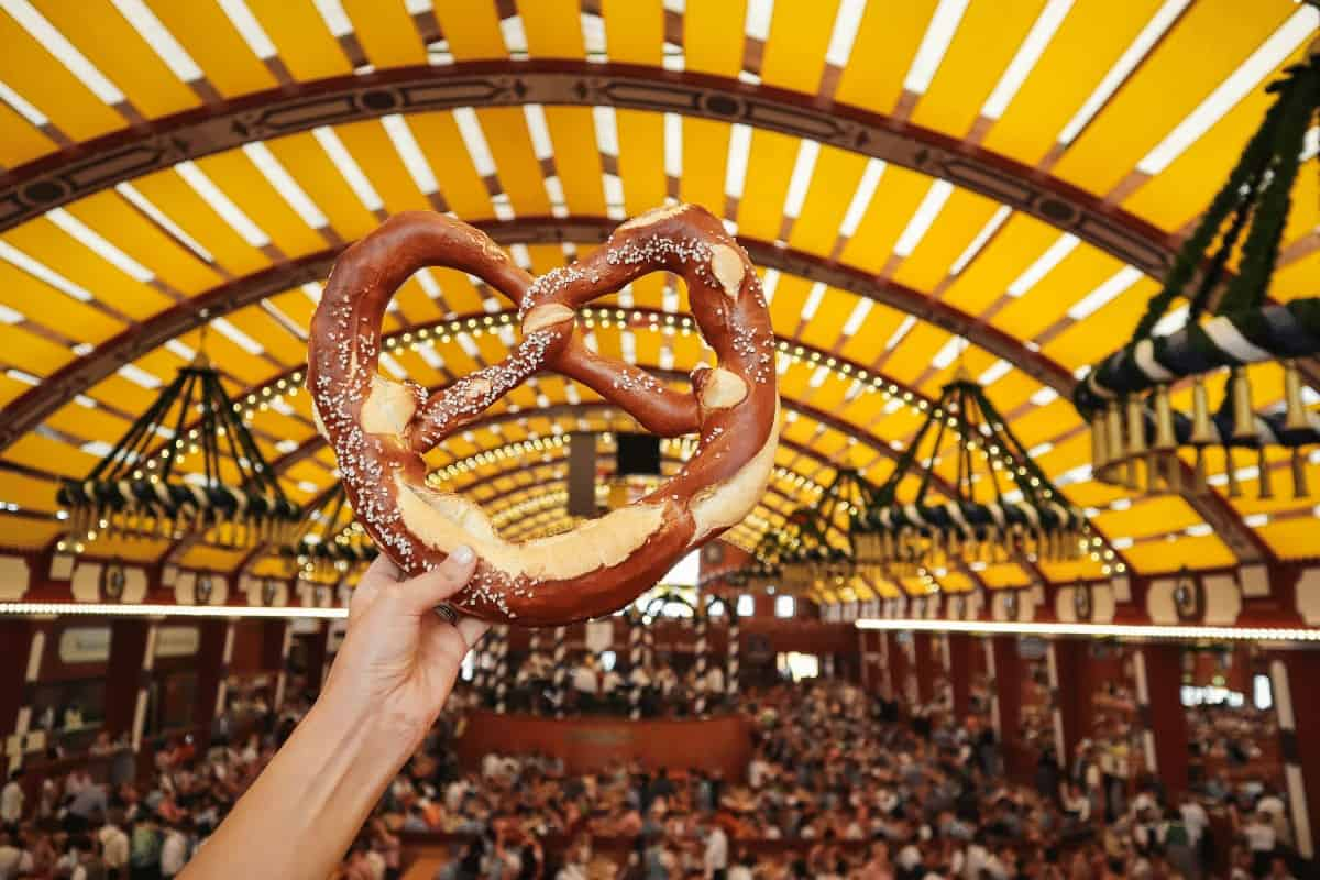 A large pretzel being held up inside a marque filled with people