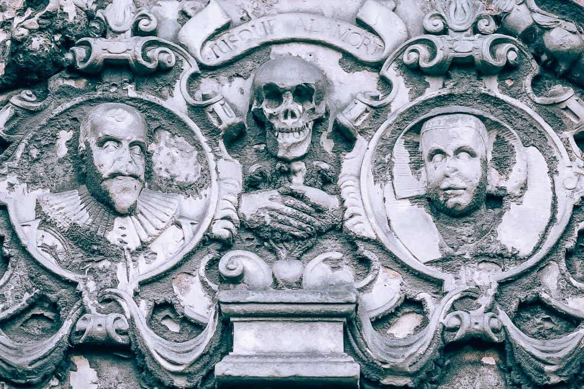 Two faces and skulls on an old deteriorating grave stone