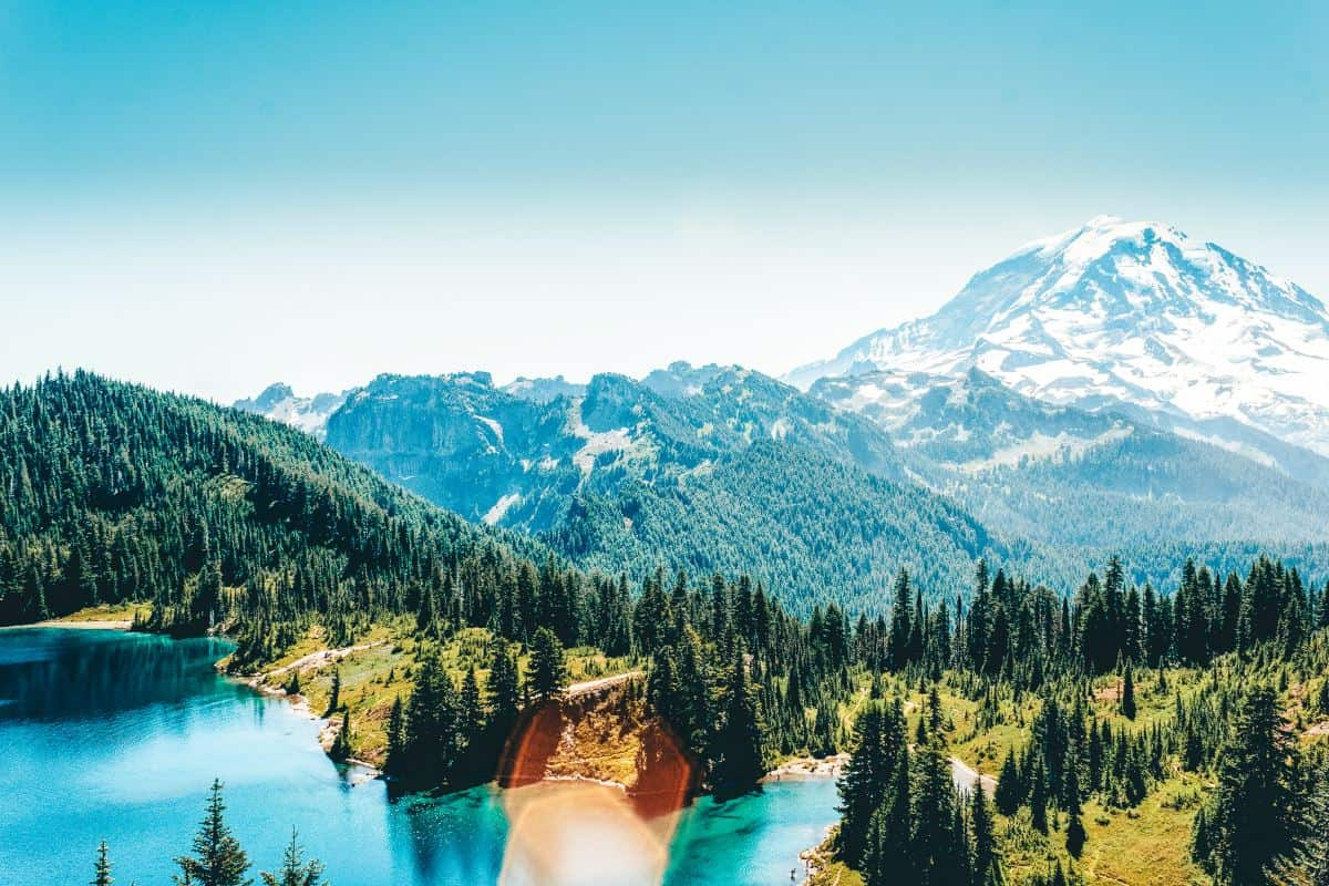 A large snow capped mountain behind a lake surrounded by trees