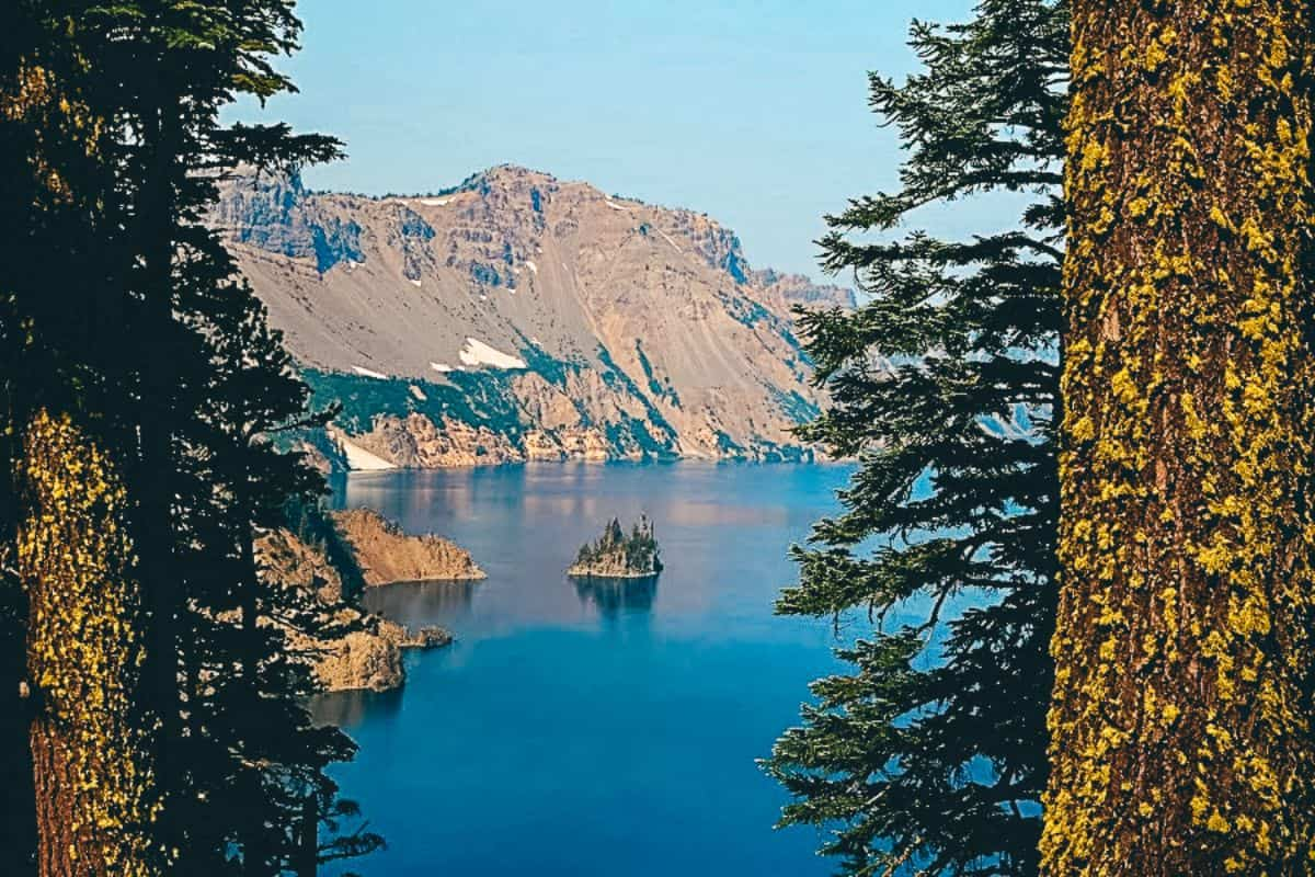 A view through the trees of a small island in the middle of a lake surrounded by rocky mountains in the Crater lake National Park in the US