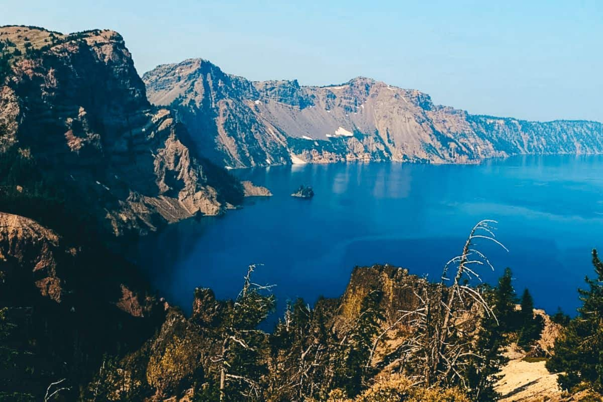 A view of the rocky mountains surrounding the blue lake at Crater Lake National Park in Oregon