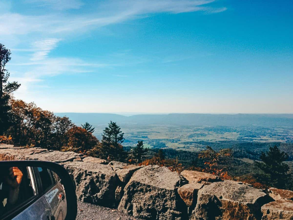 A car side mirror over looking a small rock wall to a view over the flat planes of Shenandoah National Park