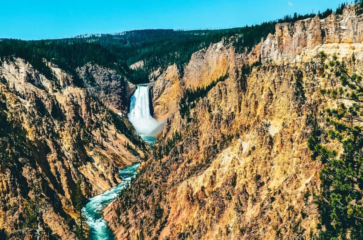 A bright blue waterfall falling between rocky cliffs