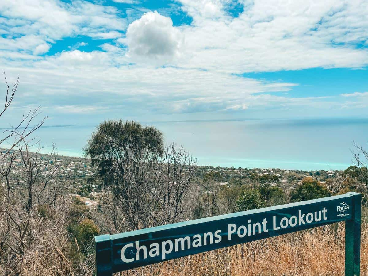 A sign reading chapmans point lookout. Looking over the ocean