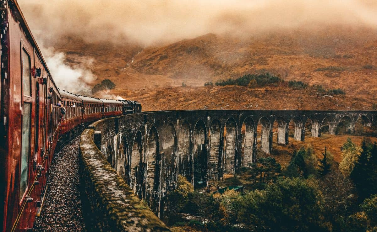 A red train crossing over a viaduct on the side of a grassy hill