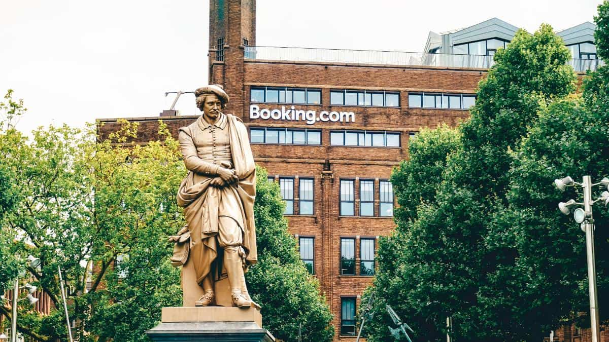 A statue of a man sitting down outside a building that reads booking.com one of the best free travel apps