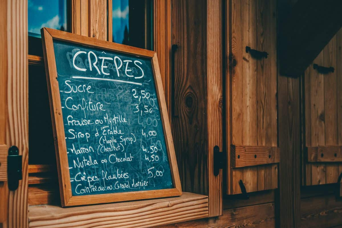 A blackboard with a menu for Crepes outside of a wooden door