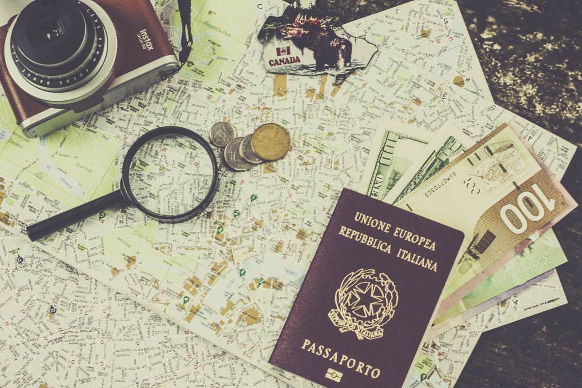 A camera, map, sticker, passport, magnifying glass and money sitting on a wooden table top
