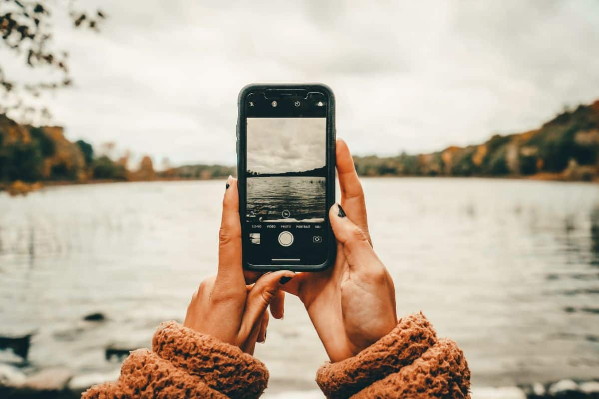 A girl holding a phone taking a photo of a lake surrounded by trees
