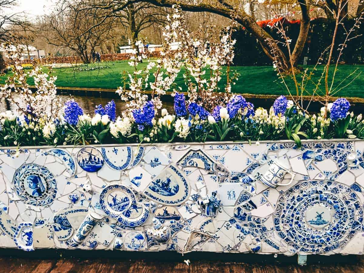 A blue mosaic planter box filled with colourful flowers