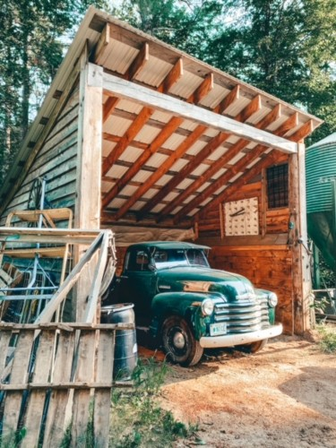 An old green truck sitting in a wooden carport