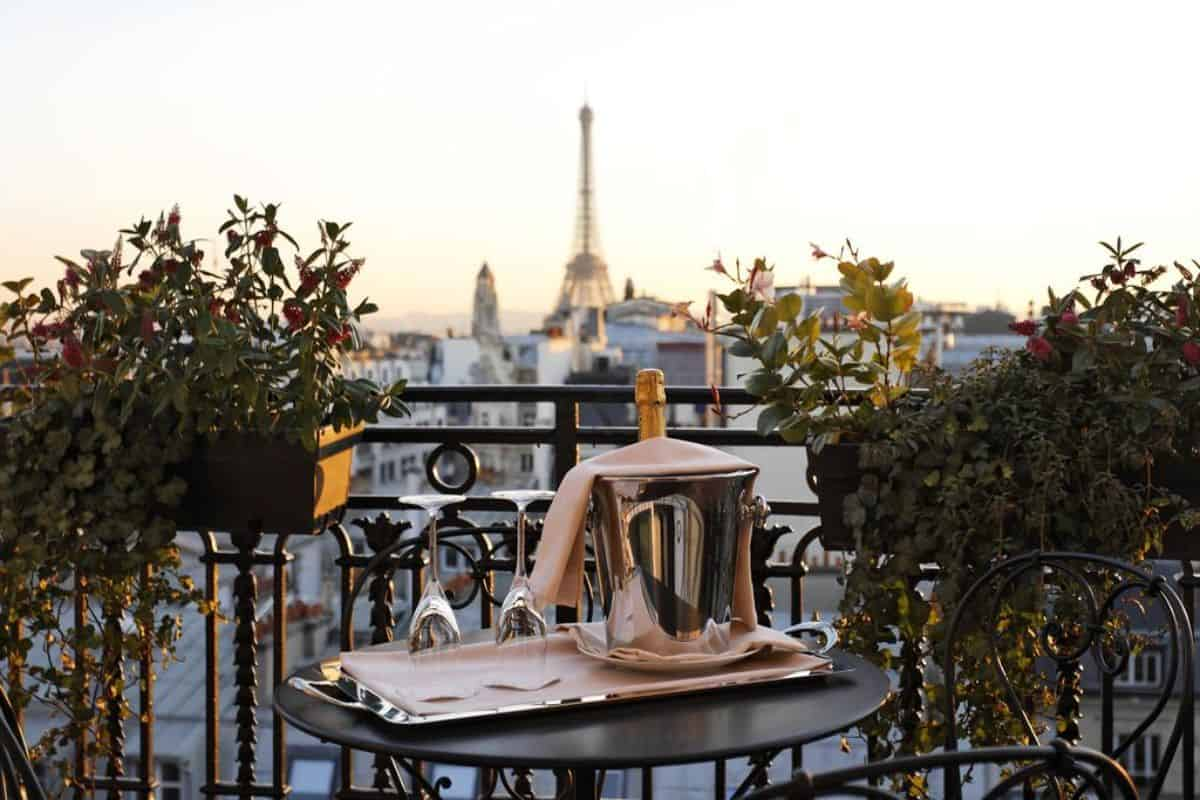 Table and chairs with a champagne bottle on a balcony over looking the Eiffel Tower