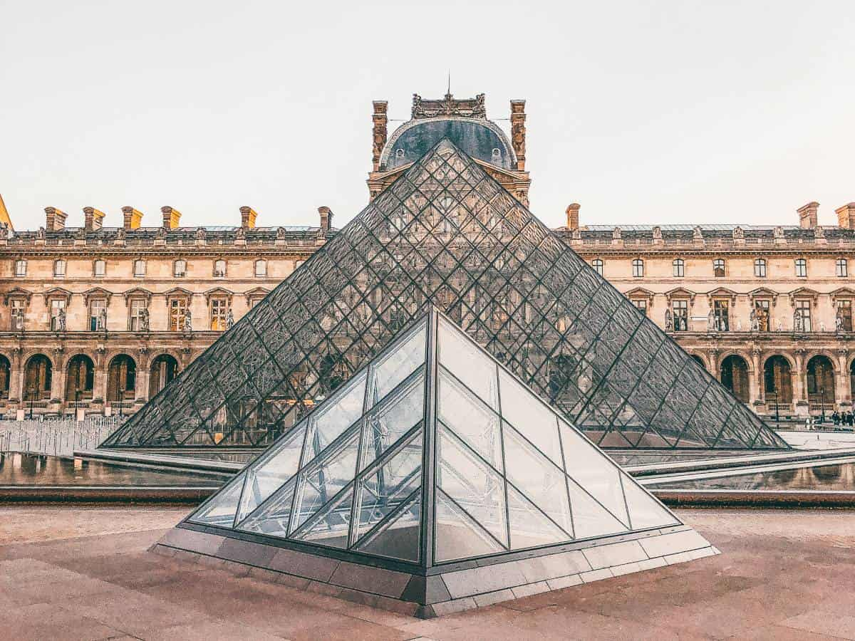Two glass triangles in front of an old Parisian building