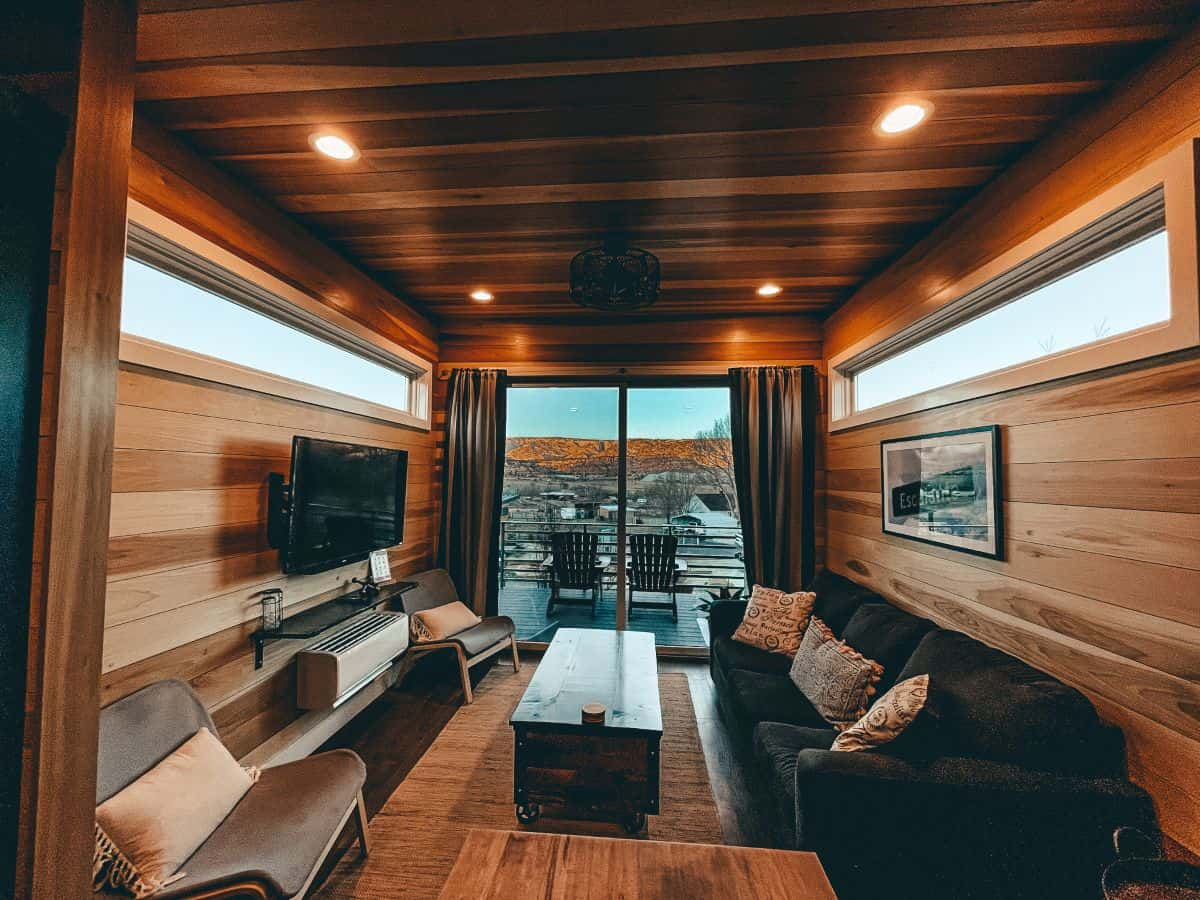 A lounge room in a wooden tiny home with a balcony looking over a rocky field