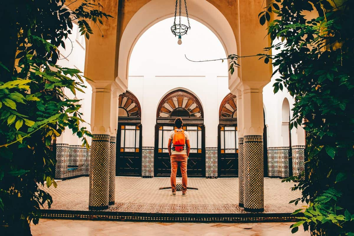 A lady standing inside the court yard at the grand mosque in Paris