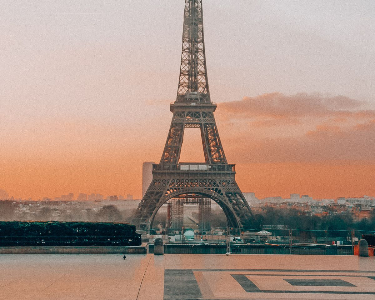 The eiffel tower at sunset in front of a court yard
