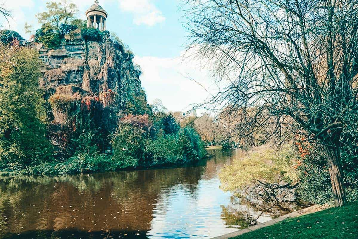 An old rotunda on top of a cliff with a river running below