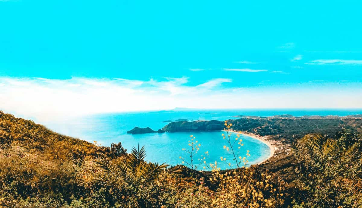 A view from the top of a shrub covered hill over the beach and ocean in Corfu