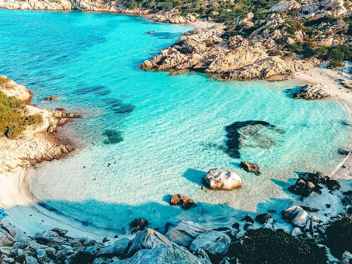 Rocky outcrops jutting into crystal blue waters in Sardinia, Italy making it one of the best beach destinations in Europe
