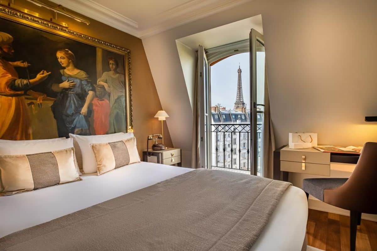 A hotel bedroom with a view of the Eiffel Tower