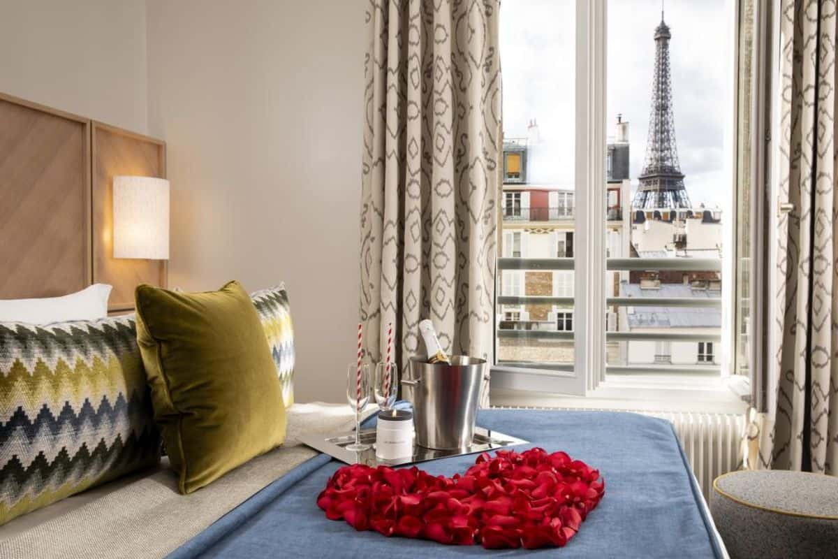 A bed with a rose petal heart overlooking a window a with a view of the Eiffel Tower