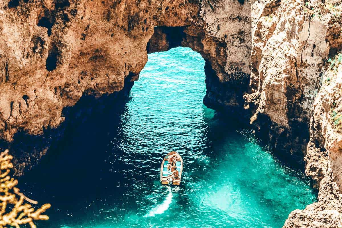A speed boat driving through a hole in a rock wall in the Algarve, Portugal