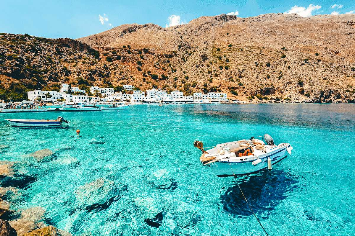 A boat floating in the crystal waters in Crete, Greece