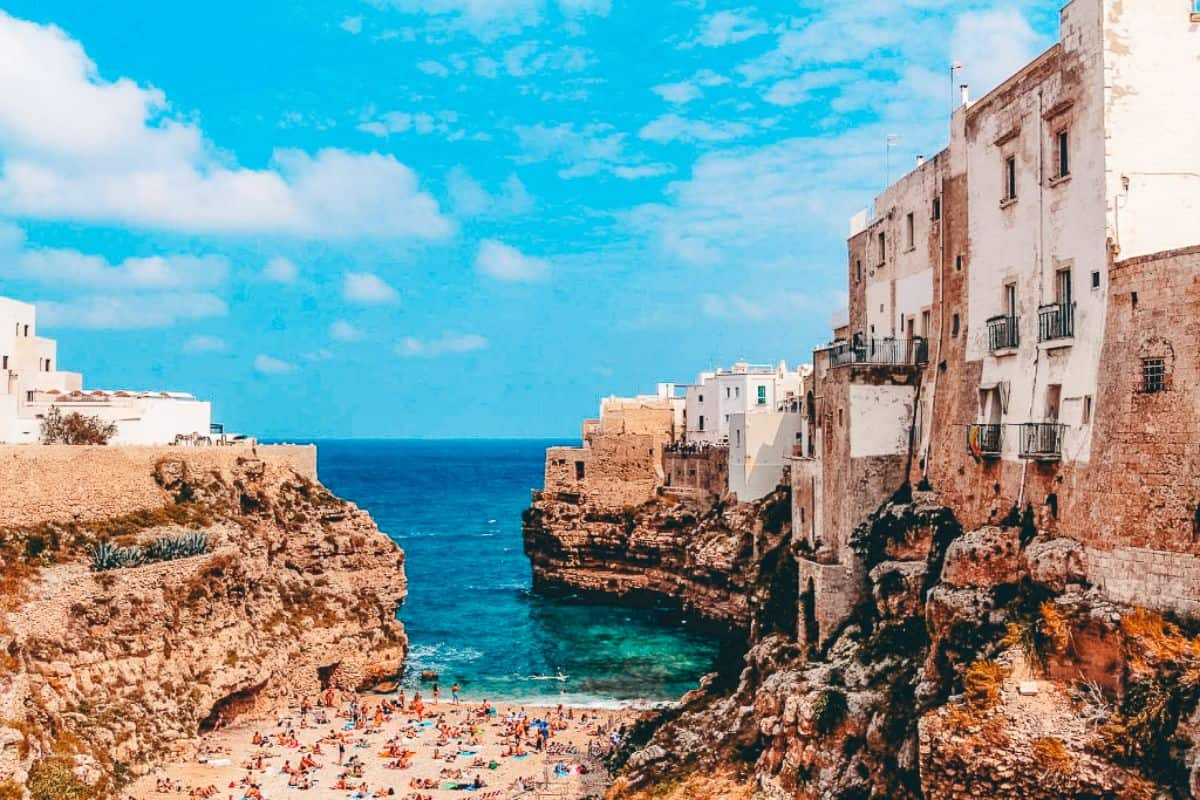 Old Italian buildings lining a small beach cove in Italy