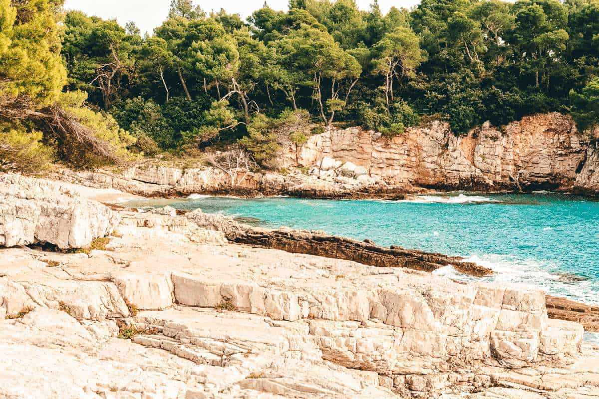 Rocky outcrop into the ocean lined with trees in Pula, Croatia
