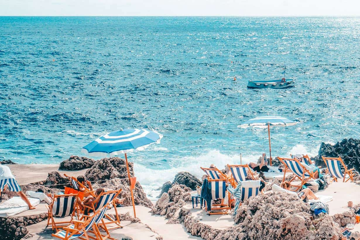 Travellers lounging in beach chairs on a beach in Capri