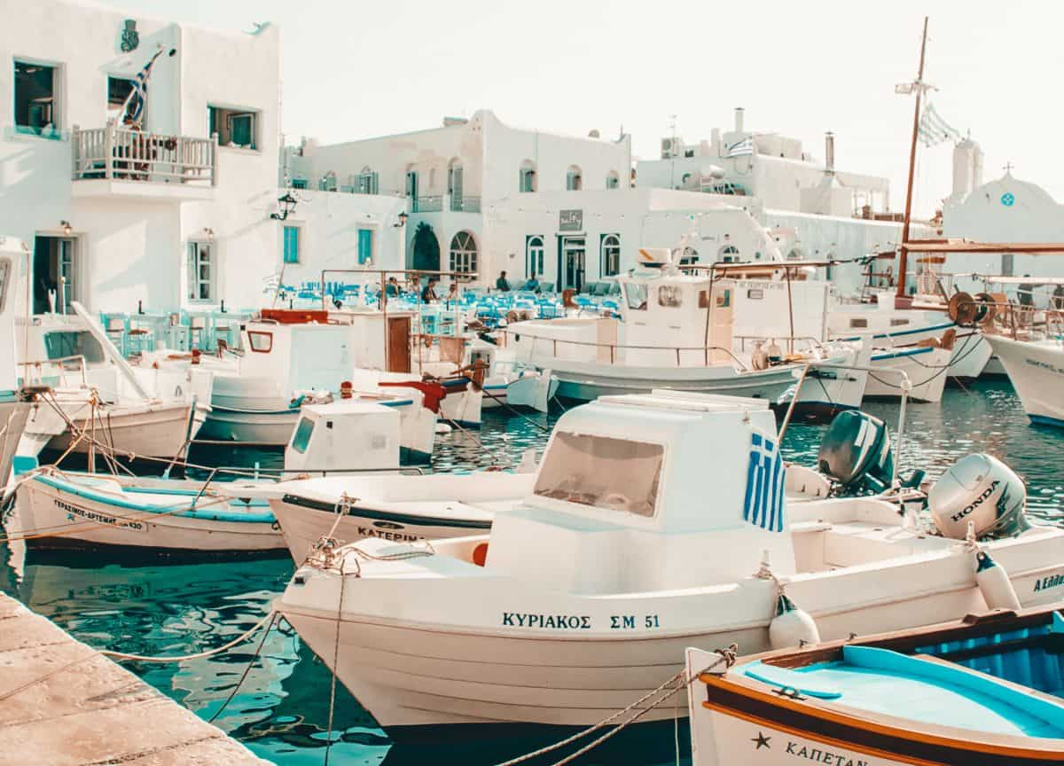 Pastle coulered boats floating in a harbour in front of white greek buildings.