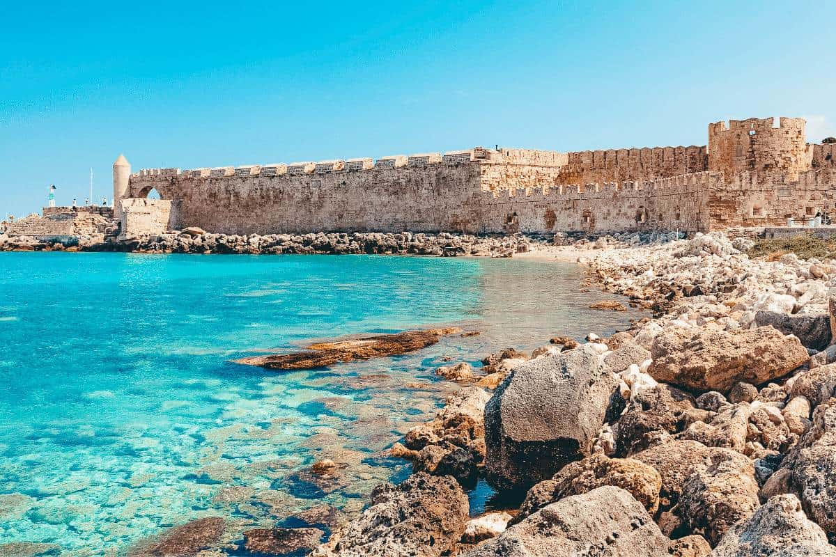 An ancient wall of a Greek ruin lining the turquoise blue ocean in Rhodes