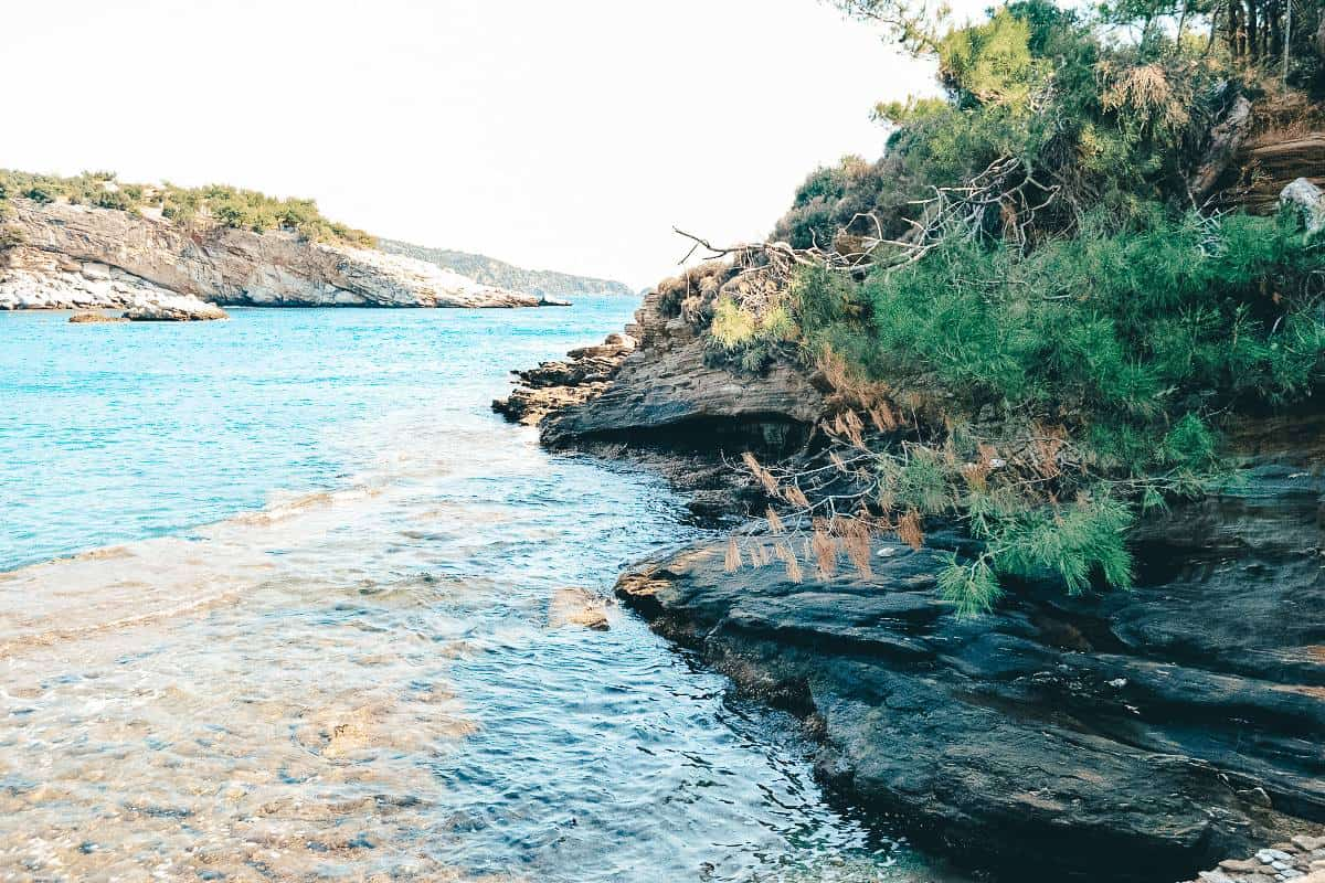 Cliff edges covered in shrubs on the edge of clear blue water in Thasos