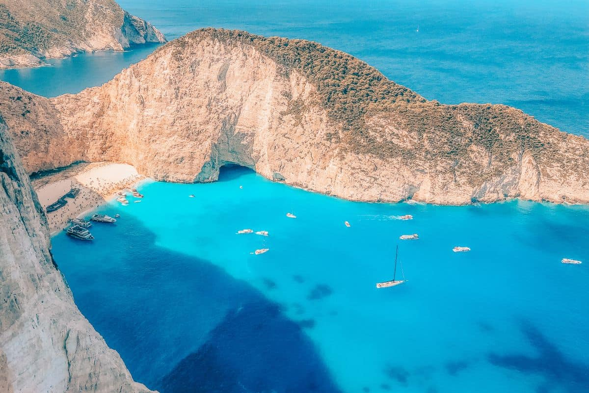 A view over the Greek Island of Zakynthos, with boats in the clear blue water surrounded by rugged cliffs