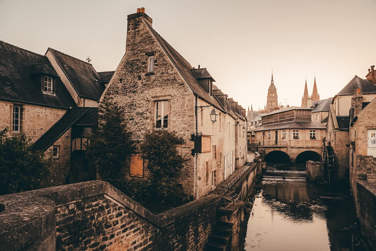 A river running through the town of Bayeux with a view of the cathedral in the background