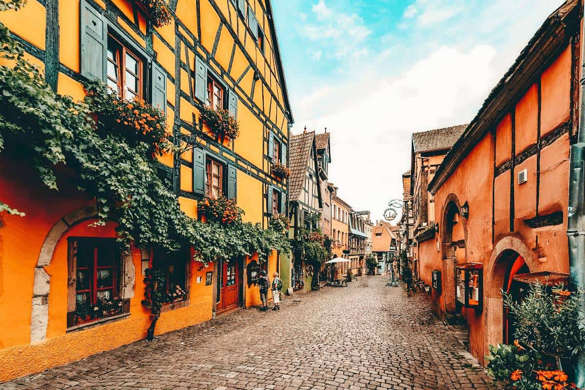 Half timber buildings lined with vines and flower boxes in Riquewihr.