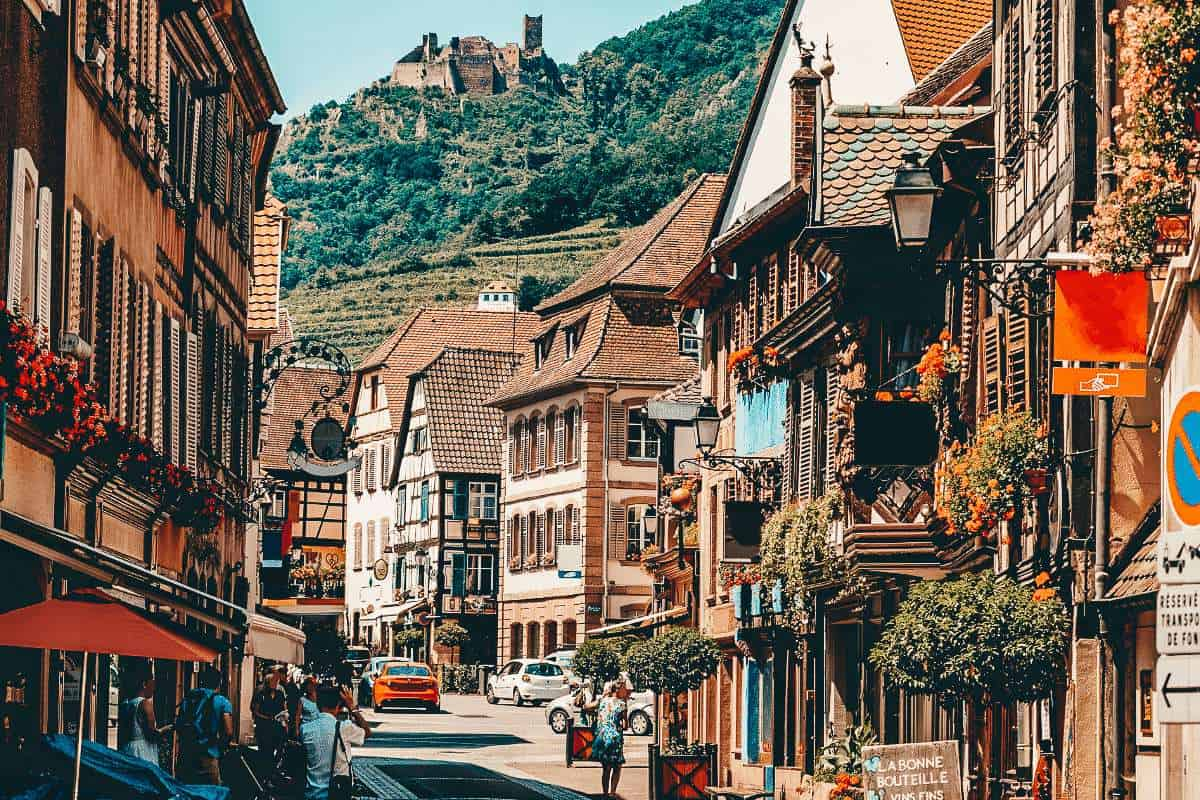 The main street in Ribeauville, one of the most beautiful towns in France. The street is lined with half timber buildings and looks up to a ruin on the hills.