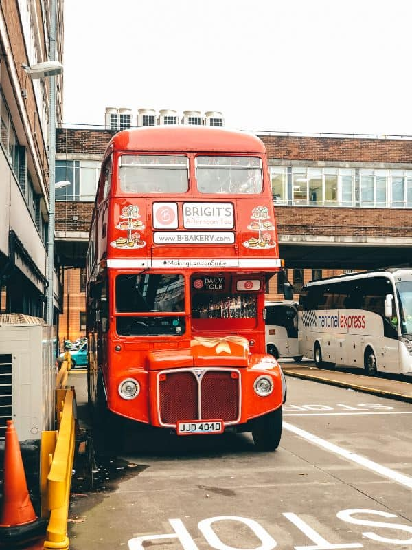 A red double decker bus parked in a bus station