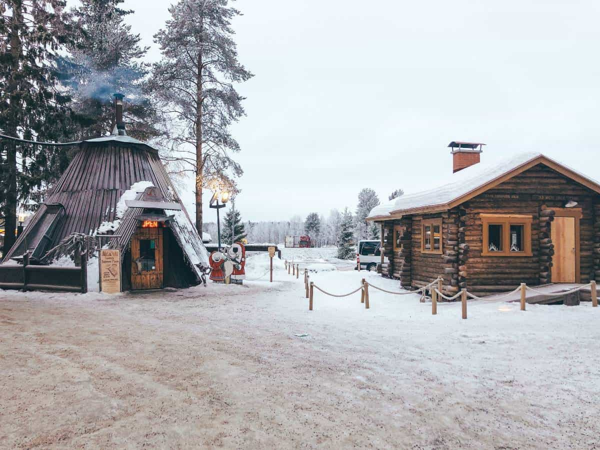 A traditional Finnish hut next to a log cabin