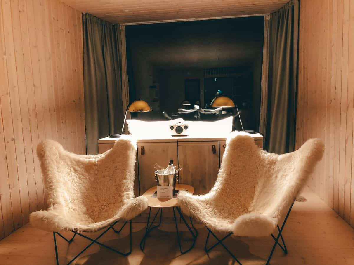 A hotel room with two fluffy chair an full length rectangle window