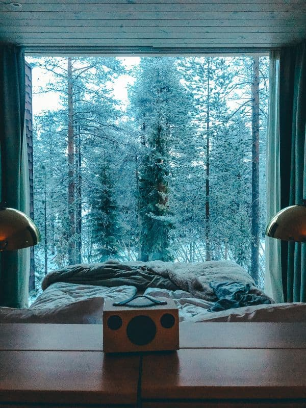 A bluetooth speaker above a bed looking out to a snowy forest