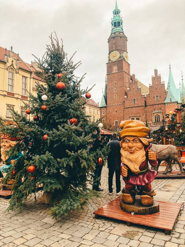A gnome standing next to a Christmas tree in Wroclaw, Poland