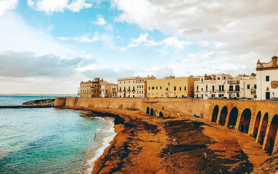 Buildings sitting on a top of a brick wall with arches lining the beach in Puglia