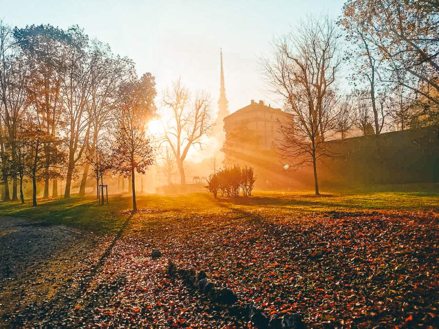 A church surrounded by autumn leaves at sunrise
