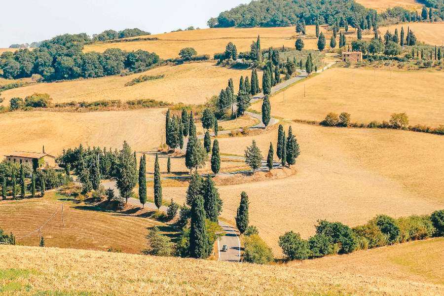 A car driving along a road in Tuscany, Italy