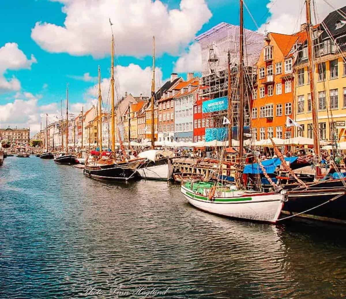 Bright coloured buildings with umbrellas and boats lining a canal on a sunny day.
