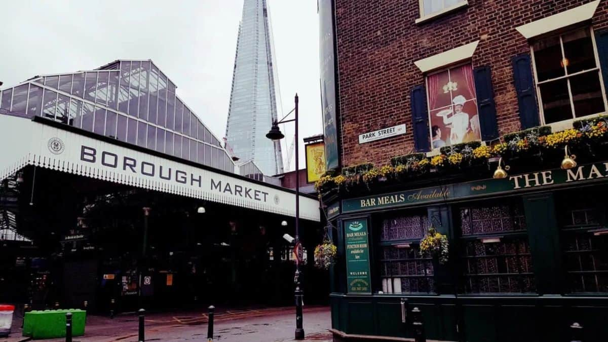 A Building labelled the borough market opposite a green and brick pub.