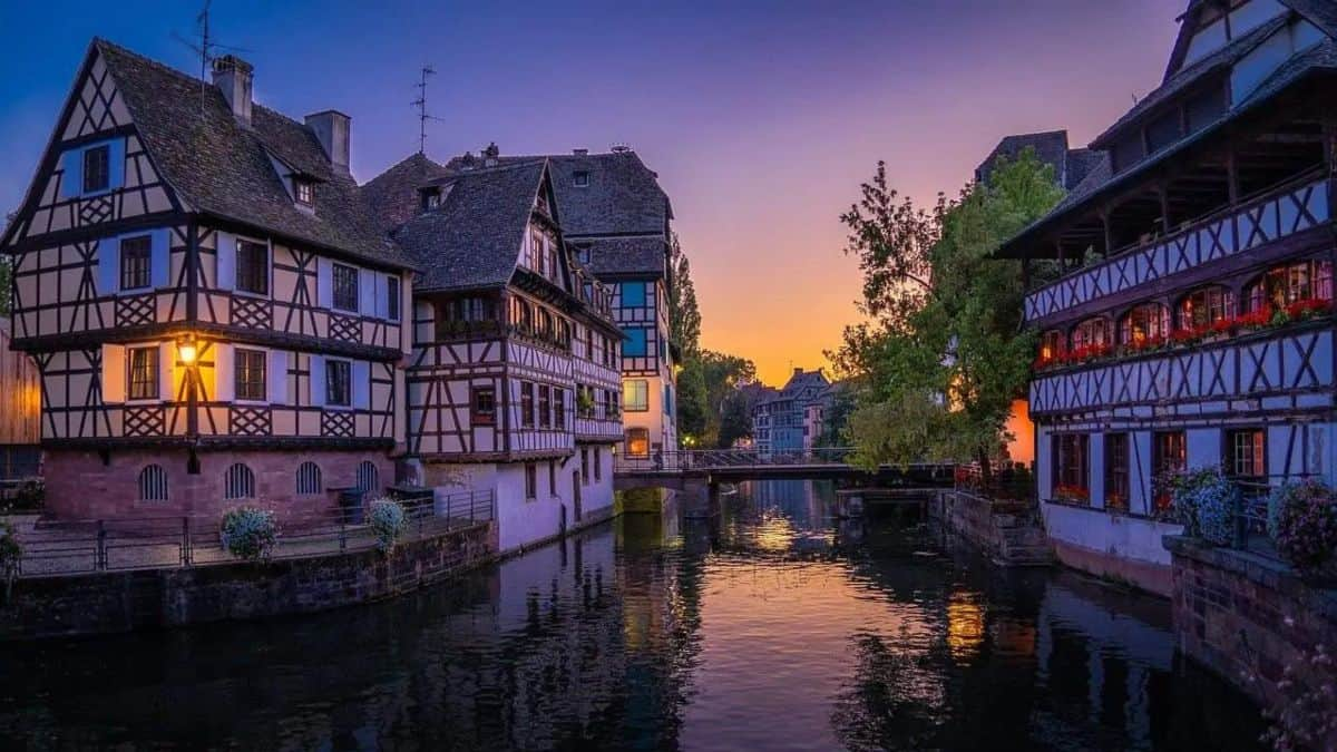 Sunset over a river with half timber houses lining the river.